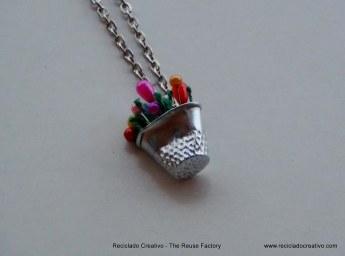 Colgante realizado con dedal y alfileres de colores. Rosa Montesa